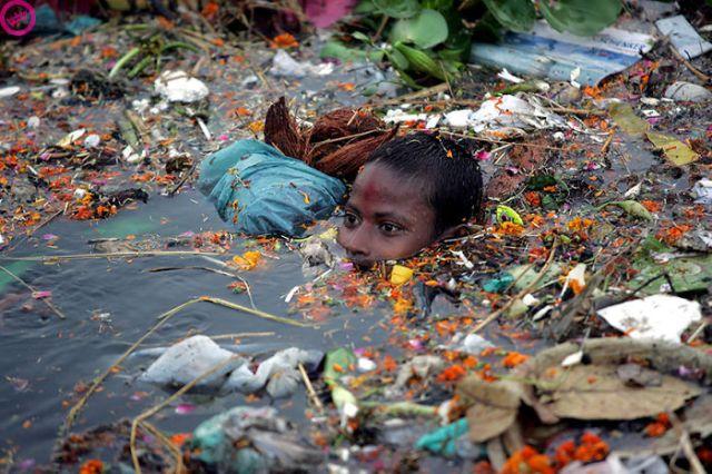 Chú bé đang bơi trong biển rác