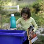 Young child placing recyclable items into large blue recycle bin (Photo by: Digital Light Source/UIG via Getty Images)